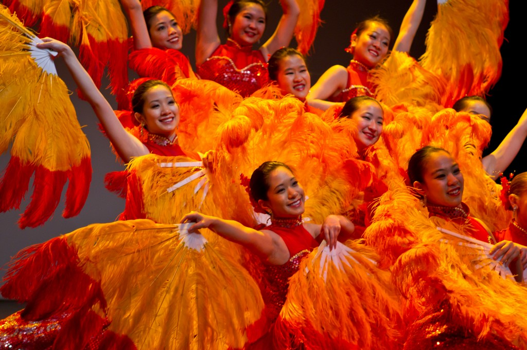 Dancers in orange costumes with feathers